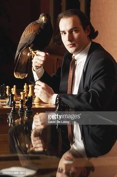 Businessman sitting by chessboard looking at bird on fist