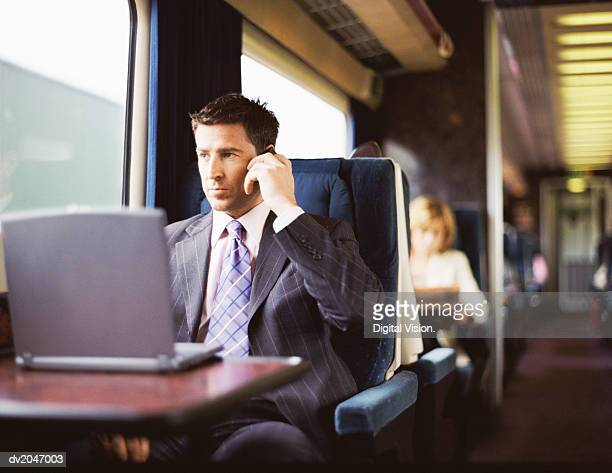 Businessman Sitting by His Laptop on a Passenger Train and Using a Mobile Phone