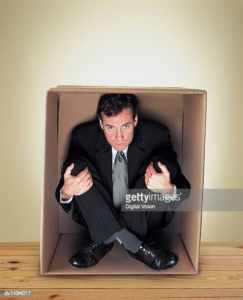 Businessman Sitting Cross Legged in a Cardboard Box