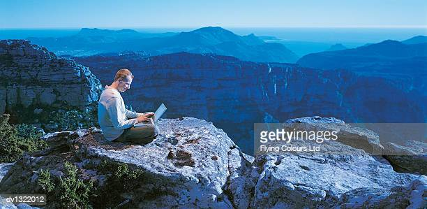 Businessman Sitting Cross-legged on a Rock High Above a Valley Using a Laptop
