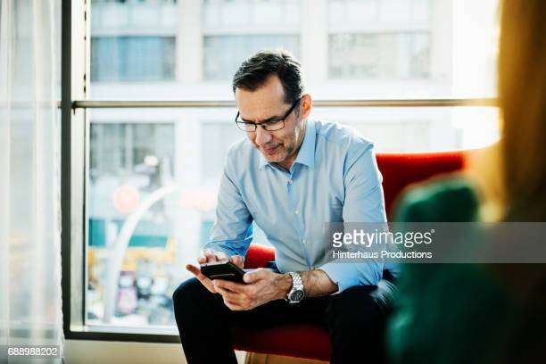 Businessman Sitting Down Looking At His phone