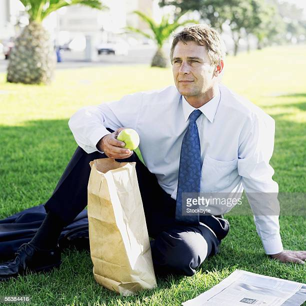 businessman sitting in a park eating an apple