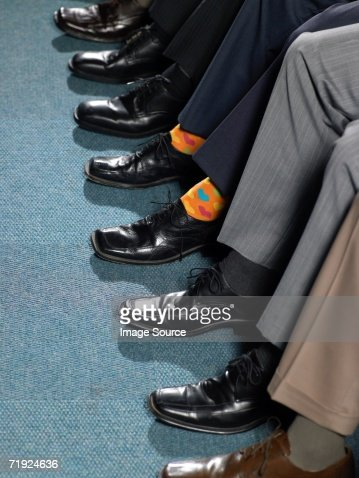 Businessman sitting in a row : Stockfoto