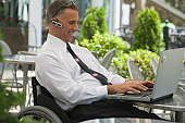 Disabled businessman sitting in a wheelchair and using a laptop