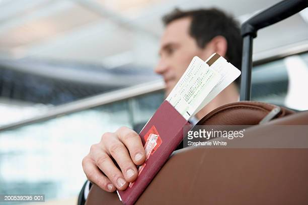 Businessman sitting in airport, holding passport and tickets
