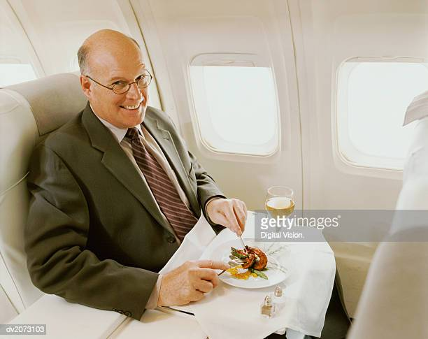Businessman Sitting in an Aircraft Eating a Meal