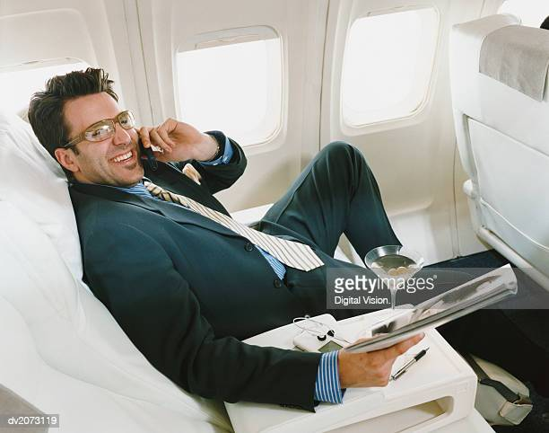 Businessman Sitting in an Aircraft Wearing Glasses and Holding a Magazine