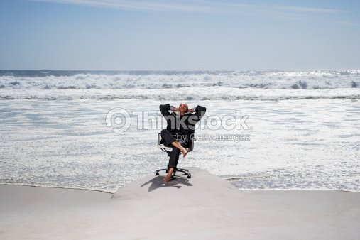 Businessman Sitting in an Office Chair at the Beach : Stock Photo