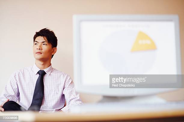 Businessman sitting in an office in front of a model of a computer monitor