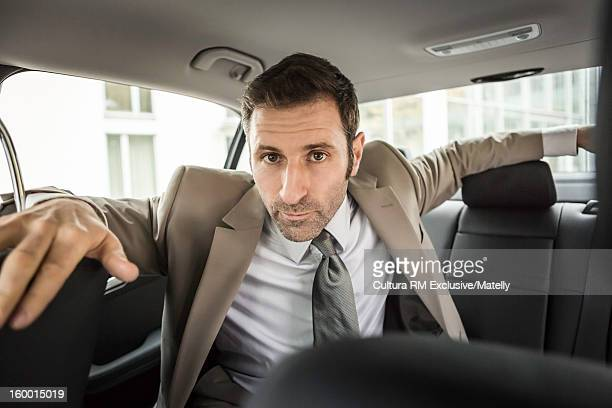 Businessman sitting in backseat of car