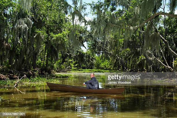 Businessman sitting in boat in swamp, side view
