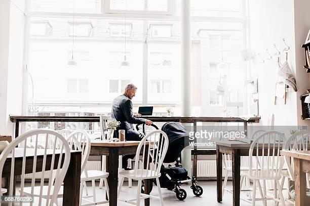 Businessman sitting in cafe with pram