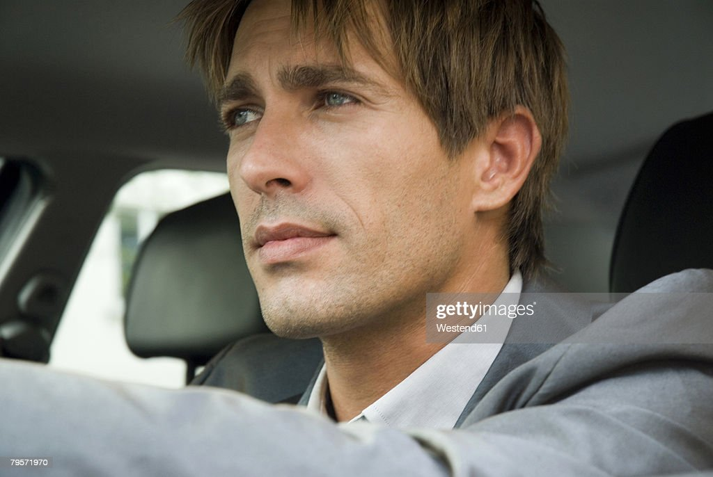 Businessman sitting in car, close-up