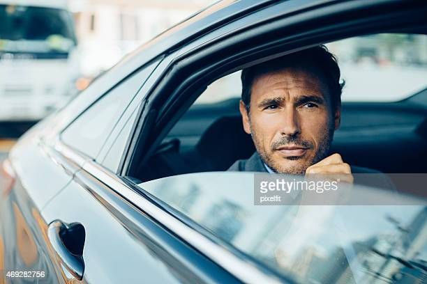Businessman sitting in car stuck in traffic