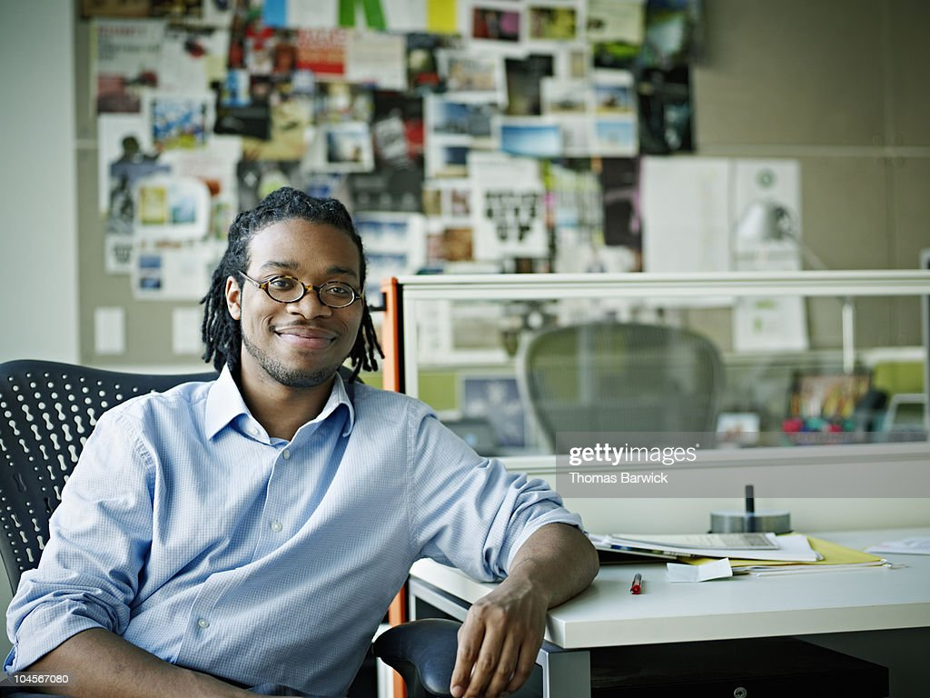 Businessman sitting in chair at desk smiling : Stock Photo