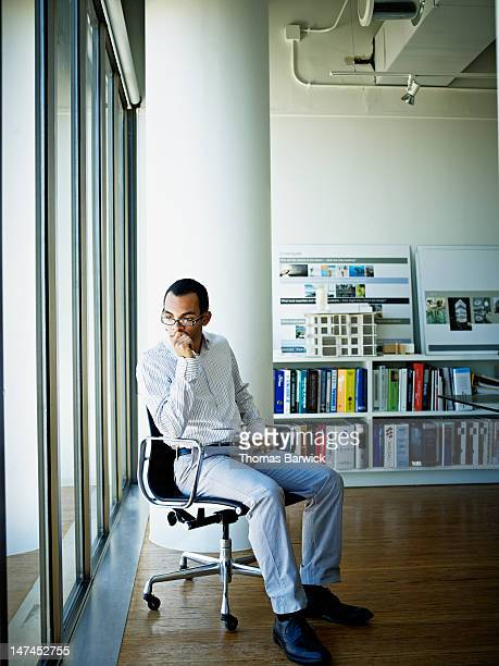 Businessman sitting in chair in office looking out