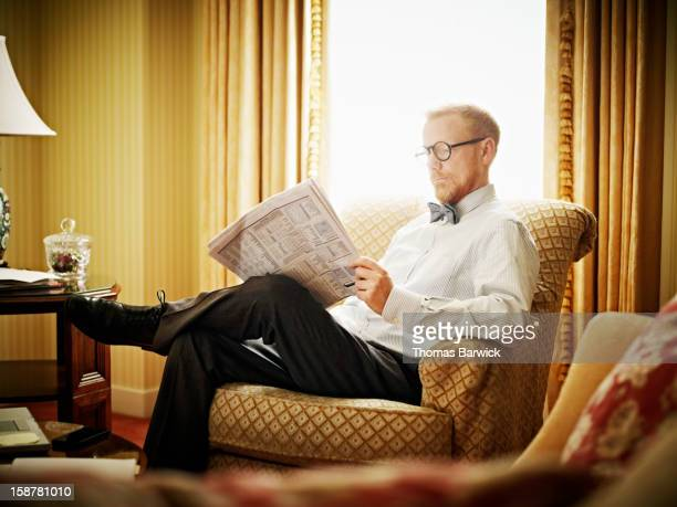 Businessman sitting in chair reading newspaper