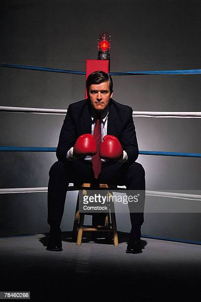 Businessman sitting in corner of boxing ring
