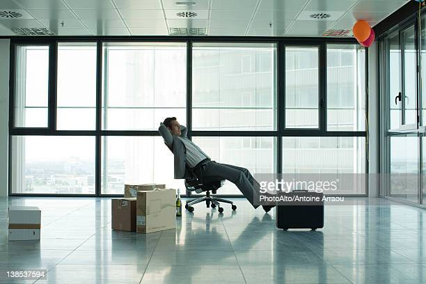 Businessman sitting in empty office with boxes on floor