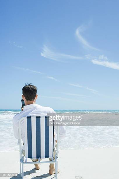 Businessman sitting in folding chair, holding up cell phone, on beach