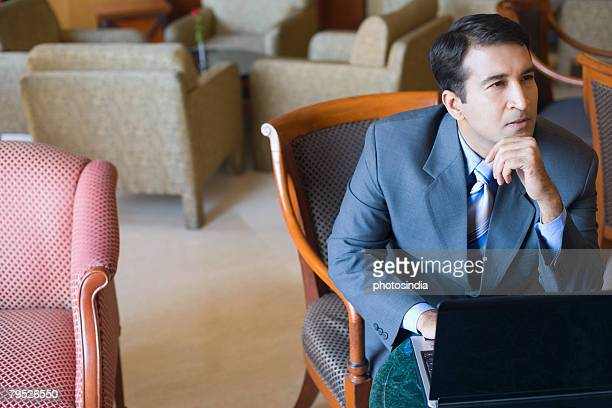 Businessman sitting in front of a laptop with his hand on his chin