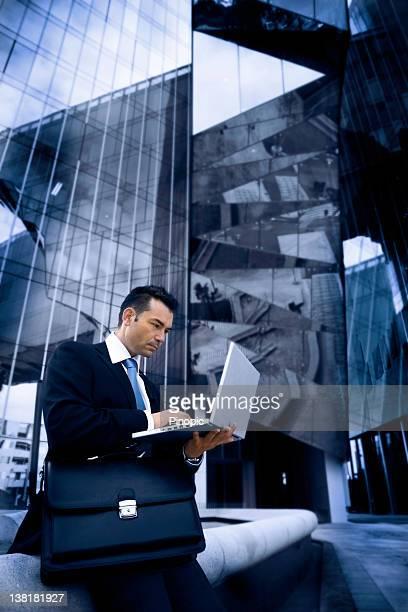 Hombre de negocios con una computadora portátil fuera moderno edificio