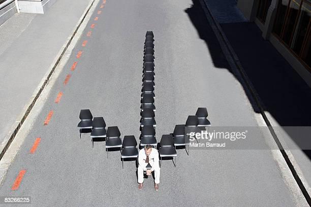 Businessman sitting in office chair in arrow-shape