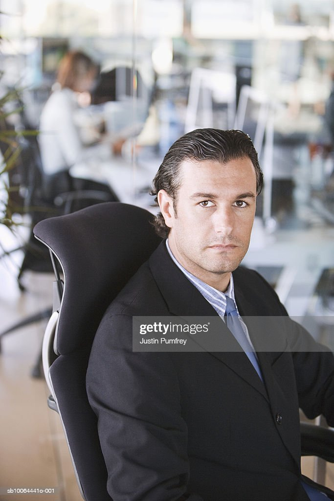 Businessman sitting in office, portrait : Stock Photo