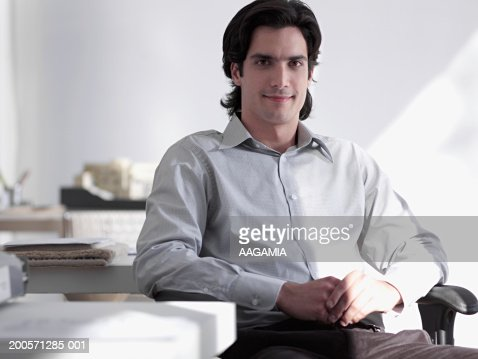 Businessman sitting in office, smiling, portrait : Stock Photo