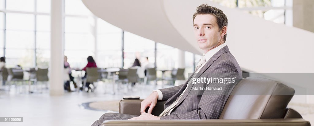 Businessman sitting in office waiting area : Stock Photo