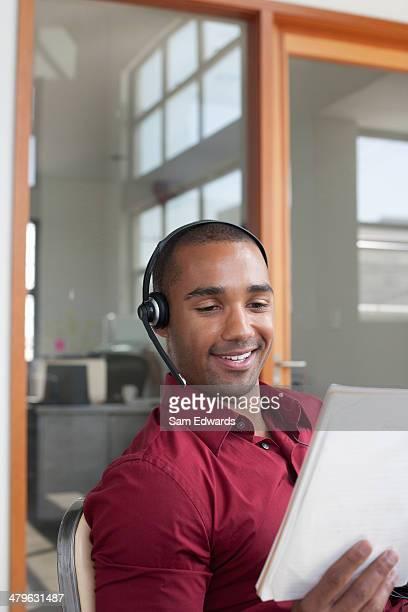 オフィス着に座っているビジネスマンハンドセット