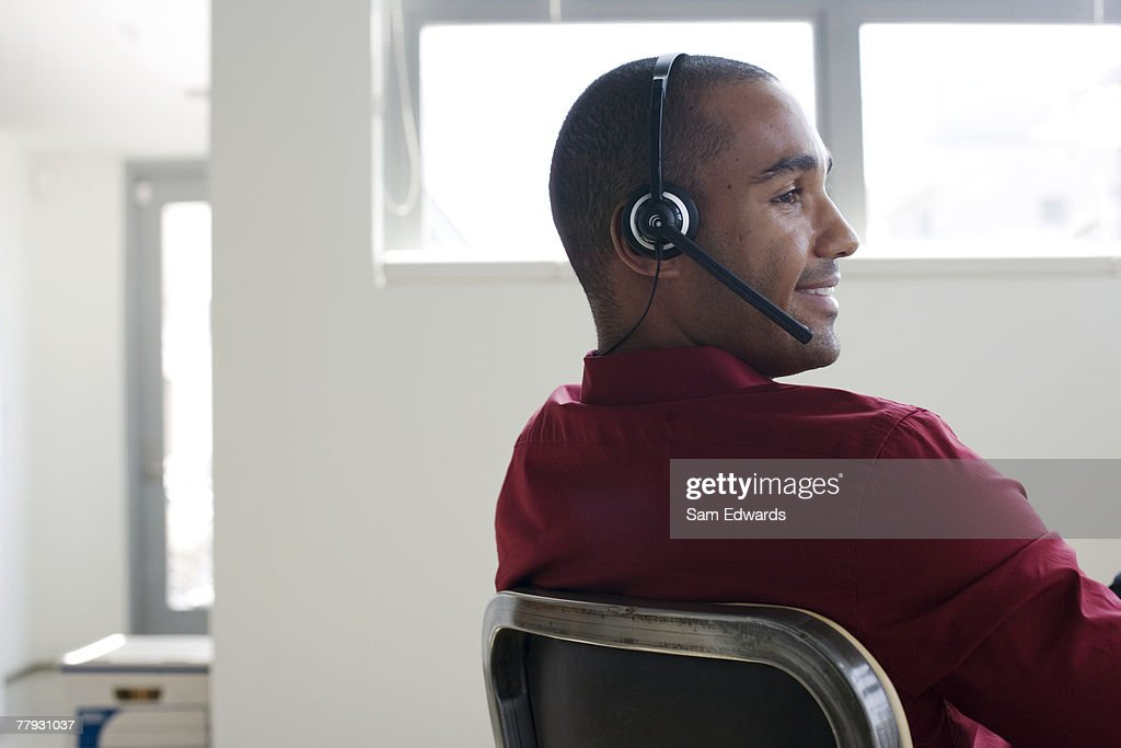 Businessman sitting in office wearing headset : Stock Photo
