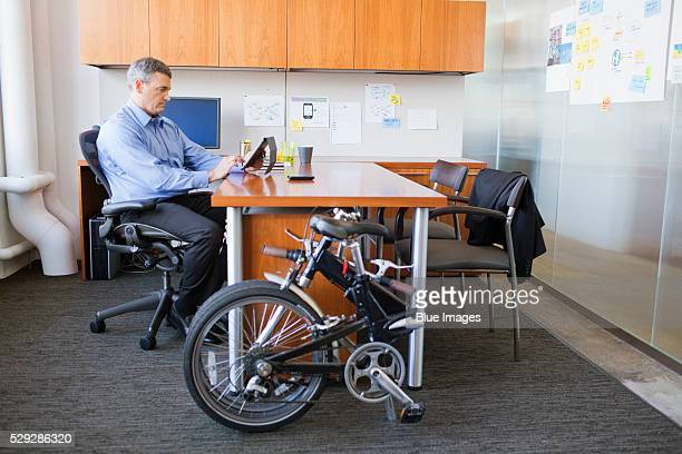 Businessman sitting in office with folded bike leaning at desk