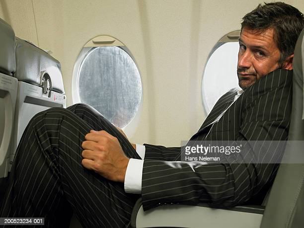 Businessman sitting in passenger seat of aero plane, portrait