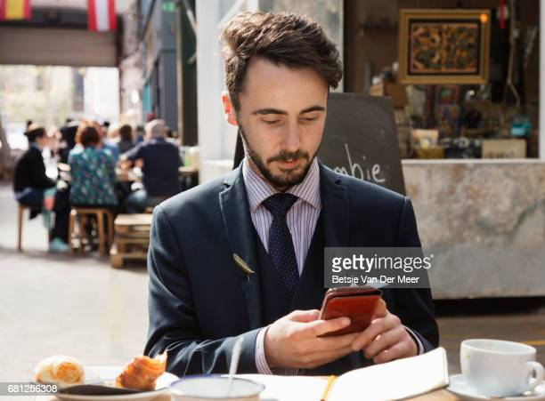 Businessman sitting in pavement cafe , looking at his phone.