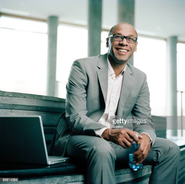 businessman sitting in stairs in office hallway