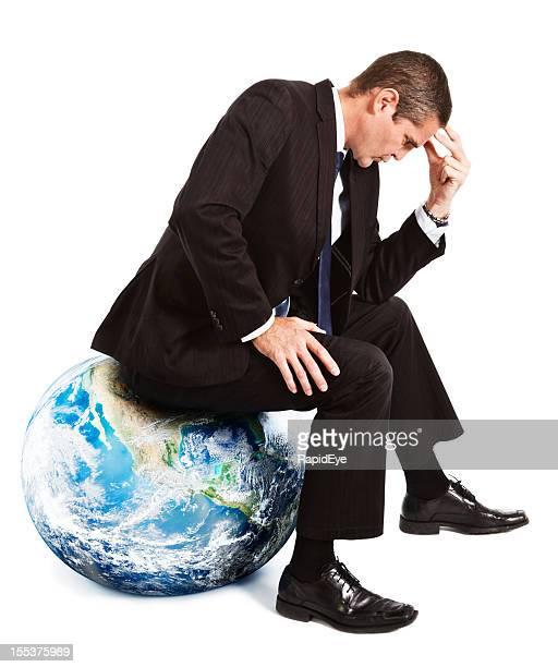 Businessman sitting in Thinker pose on Earth globe