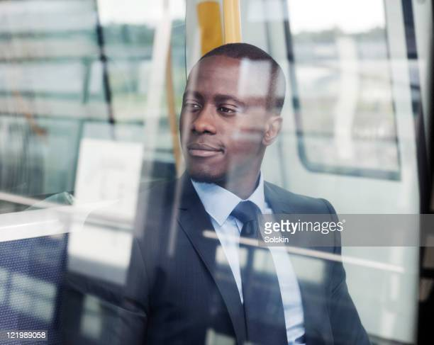 businessman sitting in train, looking out