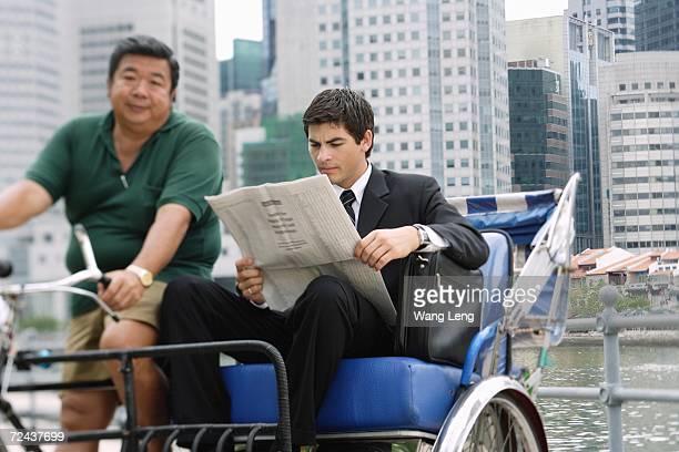 Businessman sitting in trishaw, reading newspaper