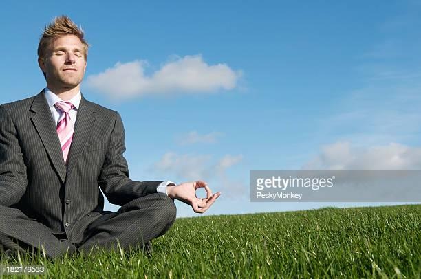 Empresario Meditando en prado verde de estar