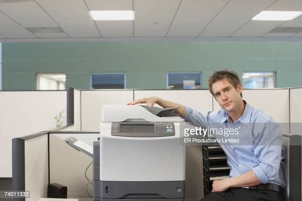 Businessman sitting next to copy machine