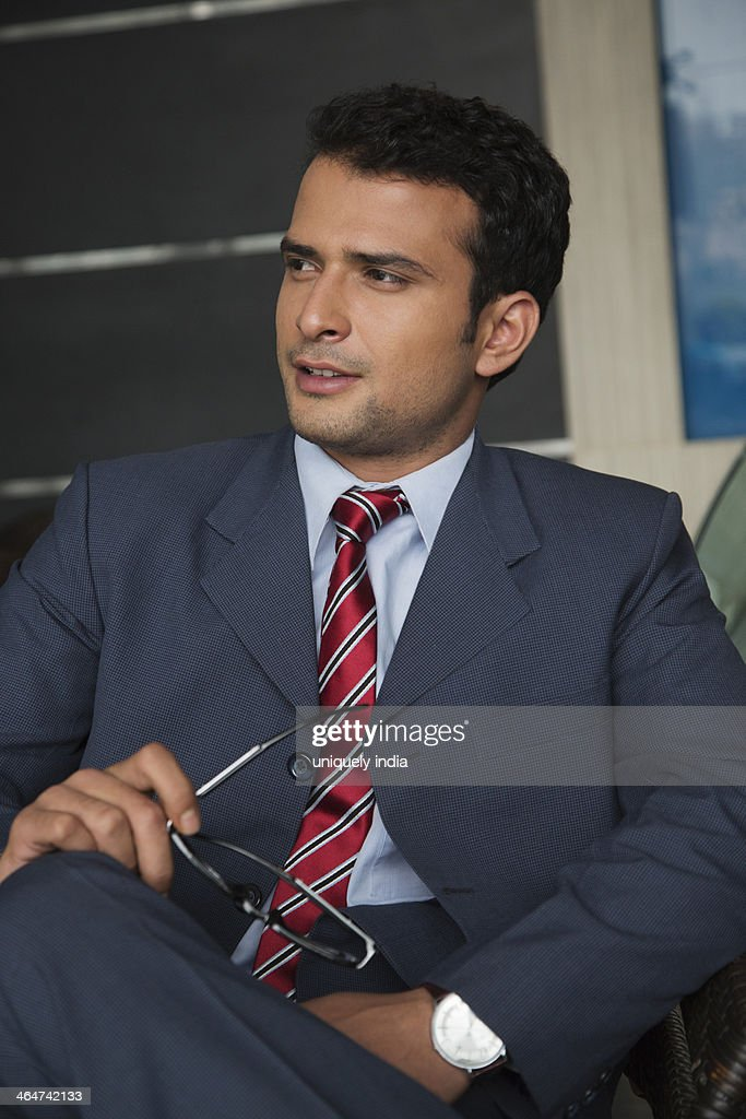 Businessman sitting on a chair and smiling : Stock Photo