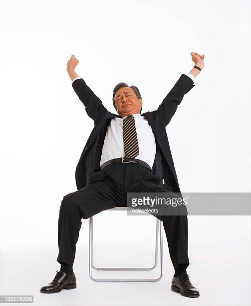 Businessman sitting on a chair and stretching