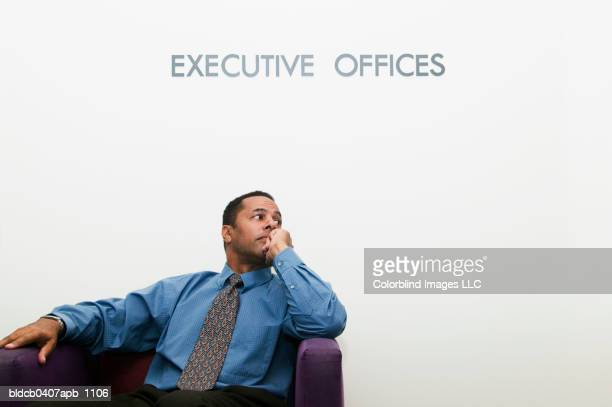 Businessman sitting on a couch in an office with his hand on his chin
