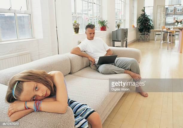 Businessman Sitting on a Sofa Working on a Laptop and His Daughter Sitting Looking Bored