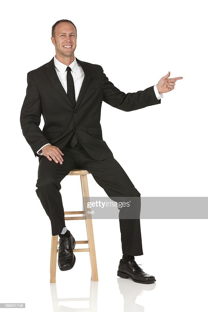 Businessman sitting on a stool and pointing