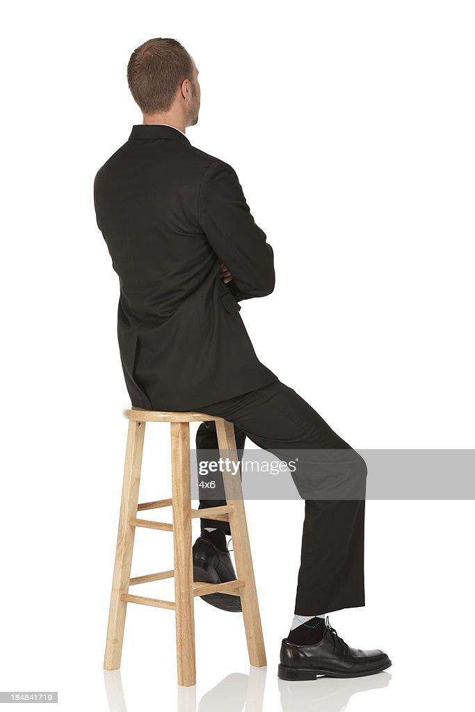 Businessman sitting on a stool