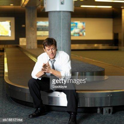 businessman sitting on baggage carousel : Stock Photo