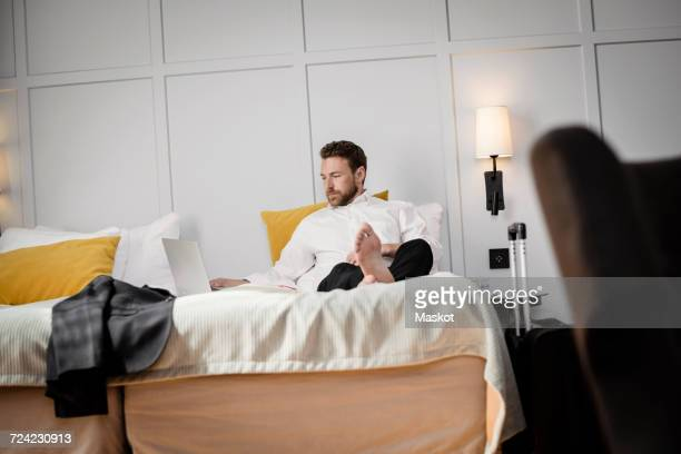 Businessman sitting on bed using laptop against wall in hotel room