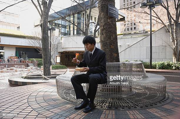 Businessman sitting on bench and having lunch